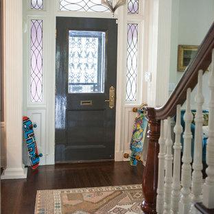 Imagen de distribuidor ecléctico, de tamaño medio, con paredes blancas, suelo de madera oscura, puerta doble, puerta metalizada y suelo rosa