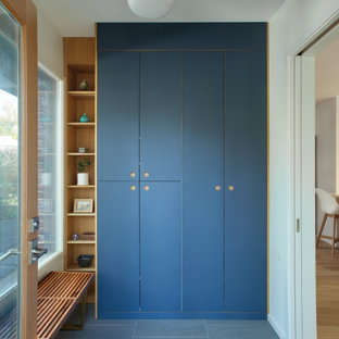 Inspiration for a mid-sized scandinavian light wood floor and gray floor entryway remodel in New York with white walls and a light wood front door