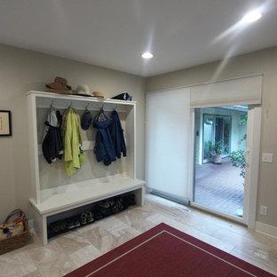 Idées déco pour une grand entrée classique avec un vestiaire, un mur gris, un sol en travertin, une porte simple, une porte blanche et un sol beige.