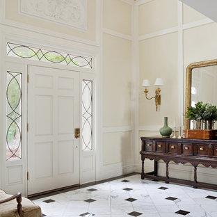 Großer Klassischer Eingang mit Foyer, beiger Wandfarbe, Einzeltür, weißer Tür und Marmorboden in Los Angeles