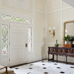 Inspiration for a large timeless marble floor entryway remodel in Los Angeles with beige walls and a white front door