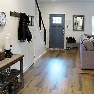 Klassisk inredning av en mellanstor ingång och ytterdörr, med vita väggar, laminatgolv, en enkeldörr, en blå dörr och brunt golv