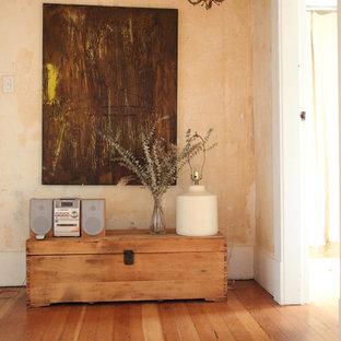 Ejemplo de entrada ecléctica con paredes beige y suelo de madera en tonos medios