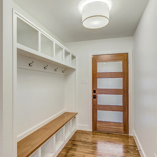 Inspiration for a mid-sized transitional light wood floor and brown floor entryway remodel in Dallas with white walls and a medium wood front door