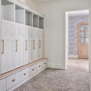 Inspiration pour une grand entrée rustique avec un vestiaire, un mur blanc et un sol en brique.