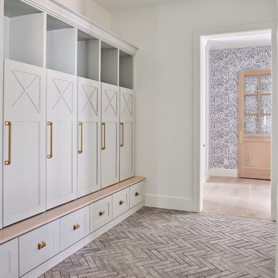 Example of a large country brick floor mudroom design in Phoenix with white walls