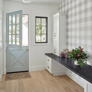Idée de décoration pour un hall d'entrée champêtre avec un sol en bois clair, un sol beige, un mur multicolore, une porte hollandaise et une porte bleue.