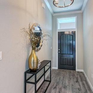 Immagine di un piccolo corridoio chic con pareti grigie, pavimento in laminato, una porta singola, una porta in legno scuro e pavimento grigio