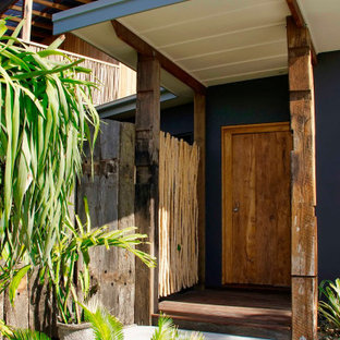 Inspiration for a tropical wood wall entryway remodel in Other with purple walls and a medium wood front door