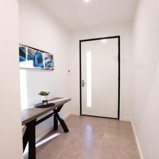 Bild på en mellanstor funkis hall, med vita väggar, klinkergolv i keramik, en enkeldörr, en vit dörr och beiget golv