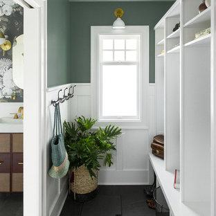 Inspiration för klassiska kapprum, med gröna väggar och svart golv
