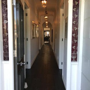 Diseño de hall casetón y panelado, clásico, pequeño, panelado, con paredes blancas, suelo de madera oscura, puerta simple, puerta de madera oscura, suelo marrón y panelado