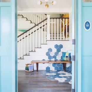 オレンジカウンティの中サイズのダッチドアビーチスタイルのおしゃれな玄関ドア (白い壁、無垢フローリング、青いドア、茶色い床) の写真