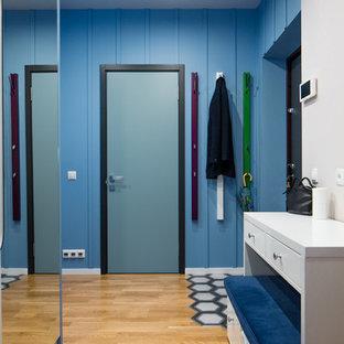 Idées déco pour une entrée contemporaine avec un couloir, un mur bleu, un sol en bois brun, une porte simple et une porte bleue.