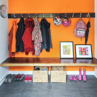Trendy gray floor entryway photo in New York with orange walls and a white front door