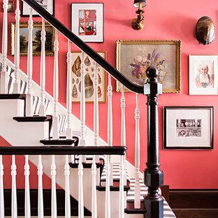 Réalisation d'un très grand hall d'entrée bohème avec un mur rose, un sol en bois foncé, une porte simple et une porte en bois foncé.
