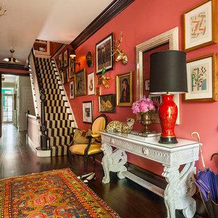 Cette photo montre un très grand hall d'entrée éclectique avec un mur rose, un sol en bois foncé, une porte simple et une porte en bois foncé.