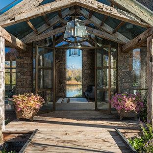 Inspiration pour une grand porte d'entrée chalet avec un sol en contreplaqué, une porte double, une porte métallisée et un mur beige.