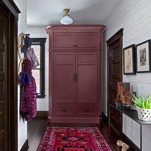 デトロイトの小さい片開きドアトラディショナルスタイルのおしゃれな玄関ホール (白い壁、濃色無垢フローリング、濃色木目調のドア、茶色い床) の写真