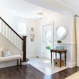 トロントの中くらいの片開きドアトランジショナルスタイルのおしゃれな玄関ドア (マルチカラーの壁、トラバーチンの床、白いドア) の写真