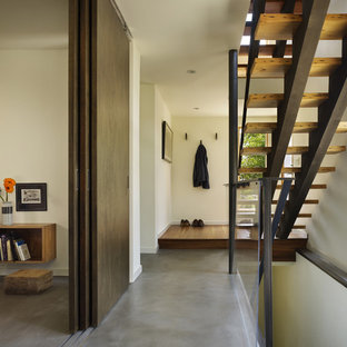Entryway - mid-sized modern concrete floor entryway idea in Seattle with white walls and a medium wood front door