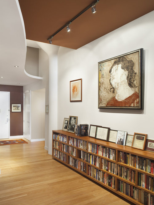 Example of a trendy light wood floor entryway design in New York with white  walls - Long Short Bookcase Houzz