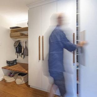Свежая идея для дизайна: маленькое фойе в современном стиле с белыми стенами, полом из бамбука, одностворчатой входной дверью, входной дверью из дерева среднего тона и коричневым полом - отличное фото интерьера