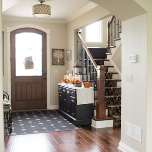 Example of a mid-sized transitional medium tone wood floor and brown floor entryway design in Other with beige walls and a medium wood front door