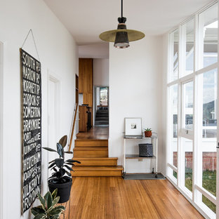 Contemporary entry hall in Hobart with white walls, medium hardwood floors and brown floor.
