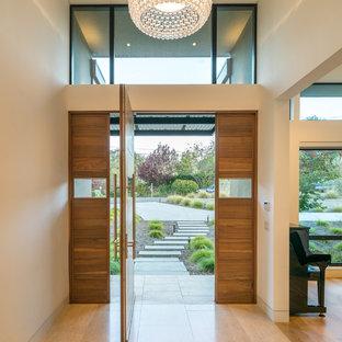 Идея дизайна: входная дверь в современном стиле с белыми стенами, поворотной входной дверью, входной дверью из дерева среднего тона и коричневым полом