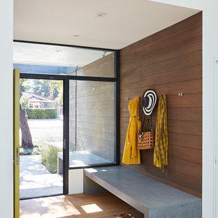 Ejemplo de entrada retro con paredes marrones y suelo de madera clara
