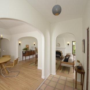 Esempio di un ingresso mediterraneo di medie dimensioni con una porta singola, una porta in legno chiaro, pareti bianche e pavimento in terracotta