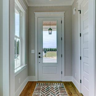 Aménagement d'un petit hall d'entrée campagne avec un mur gris, un sol en brique, une porte simple, une porte blanche et un sol rouge.