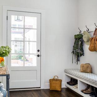 Modelo de vestíbulo posterior costero con paredes blancas, suelo de madera oscura, puerta simple, puerta de vidrio y suelo marrón