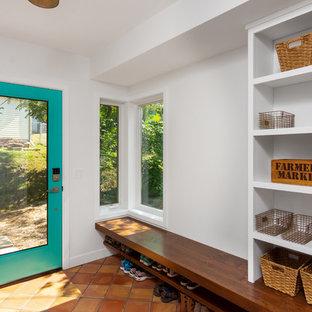 Cette photo montre une entrée nature avec un vestiaire, un mur blanc, un sol en carreau de terre cuite et un sol orange.