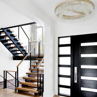Example of a transitional medium tone wood floor and brown floor entryway design in DC Metro with white walls and a black front door