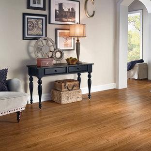 Réalisation d'une entrée tradition de taille moyenne avec un mur beige, un sol en bois clair et un sol marron.
