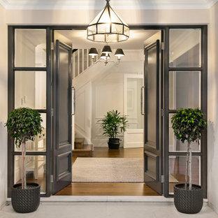 シドニーの大きい両開きドアコンテンポラリースタイルのおしゃれな玄関ドア (ベージュの壁、黒いドア、グレーの床、トラバーチンの床) の写真