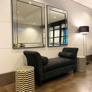 Entryway - large modern ceramic floor and brown floor entryway idea in Melbourne with white walls and a metal front door