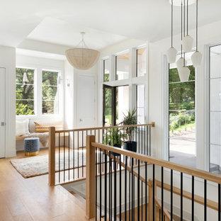 Свежая идея для дизайна: большое фойе в морском стиле с белыми стенами, светлым паркетным полом, одностворчатой входной дверью, стеклянной входной дверью, коричневым полом и кессонным потолком - отличное фото интерьера