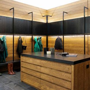 Cette image montre une très grand entrée design avec un sol en ardoise, un vestiaire et un mur noir.
