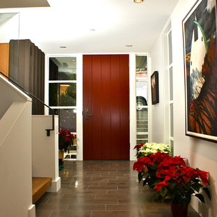 Example of a trendy ceramic floor and gray floor entryway design in Seattle with a red front door