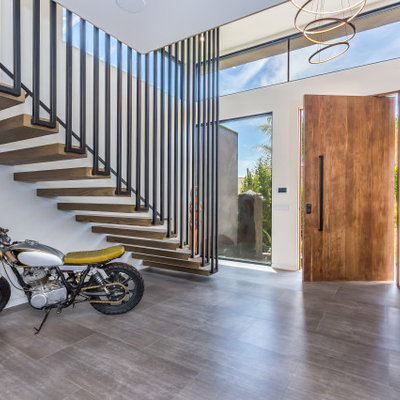 Large trendy gray floor entryway photo in Los Angeles with white walls and a medium wood front door
