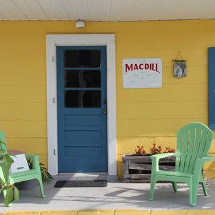Foto de puerta principal marinera, pequeña, con paredes amarillas, suelo de cemento, puerta simple y puerta azul