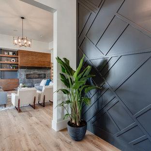 На фото: фойе в стиле модернизм с черными стенами, светлым паркетным полом, одностворчатой входной дверью и входной дверью из темного дерева с