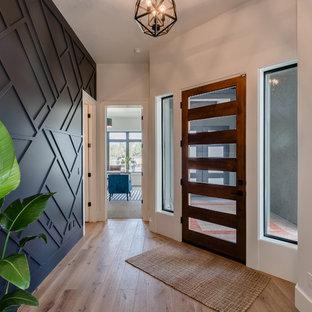 Esempio di un ingresso minimal con pareti nere, parquet chiaro, una porta singola, una porta in legno scuro e pavimento marrone
