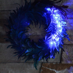 The Firefly Garden - Mad Haberdashery Wreath - Small - Add a little spice to your home with our Mad Haberdashery wreath. This playful departure from traditional evergreen decor, featuring blue and iridescent peacock feathers with blueberry accents, brings a flirtatious charm to any setting.
