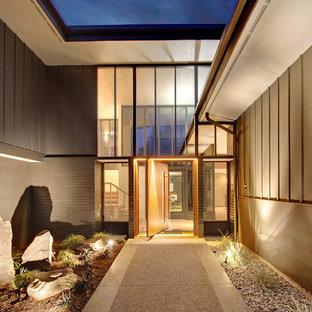 Diseño de puerta principal vintage, de tamaño medio, con puerta pivotante, puerta de madera clara, paredes grises, suelo de cemento y suelo gris
