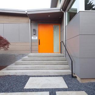 Foto de puerta principal actual, de tamaño medio, con paredes grises, suelo de cemento, puerta pivotante y puerta naranja