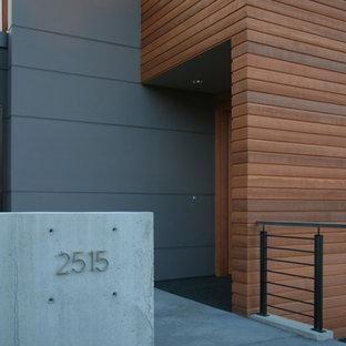 Idee per un ingresso o corridoio minimalista con una porta singola e una porta in legno bruno
